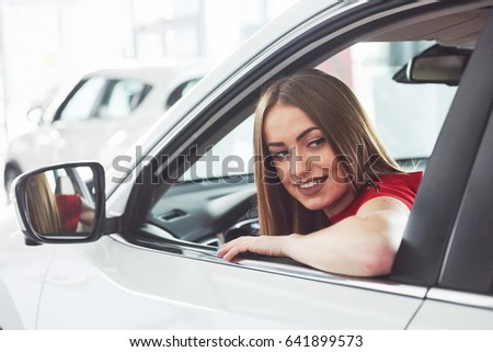 woman in car indoor keeps wheel turning around smiling looking at passengers in back seat idea taxi driver against sunset rays Light shine sky Concept of exam Vehicle - second home the girl #641899573