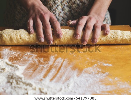Woman kneading dough on a table #641997085