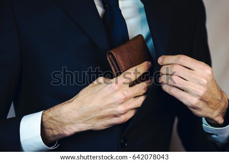 Man pulled out of his inside jacket pocket wallet Royalty-Free Stock Photo #642078043