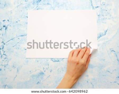 Woman's hand turning over sheet of paper #642098962