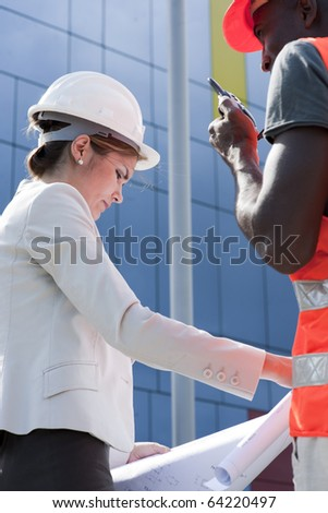 Young female engineer discussing a building project with a construction worker #64220497