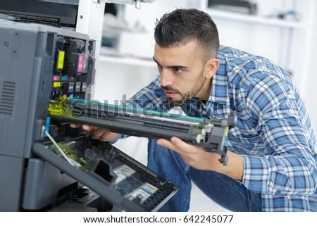 closeup shot young male technician repairing digital photocopier machine #642245077