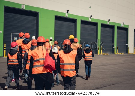 A group of people in orange helmets and reflective vests visiting factory or warehouse. From behind view. #642398374