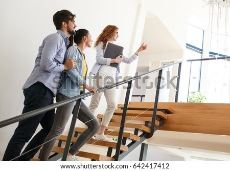 Female Real Estate agent shows interior to young couple. #642417412