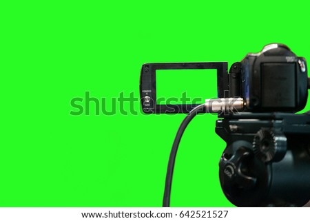 A video camera on a green background with a view from behind. Camera screen with green background #642521527