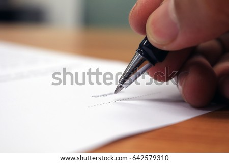 Close up of businessman hand holding a pen writing signature MOU for successful business. - Selective focus a pen. #642579310