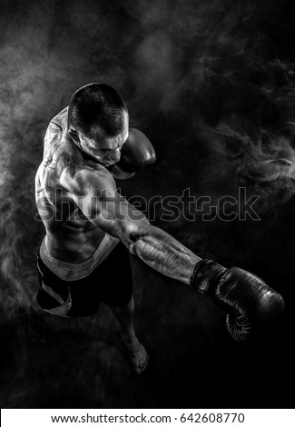 Muscular kickbox or muay thai fighter punching in smoke. Royalty-Free Stock Photo #642608770