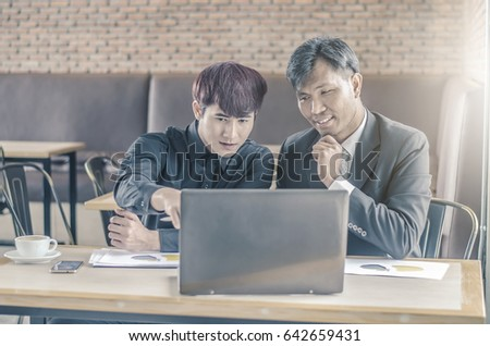 Two attractive businessmen having a meeting with laptop while having coffee in a coffee shop's . #642659431