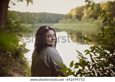 beautiful girl sitting by the river and smiling #642694753