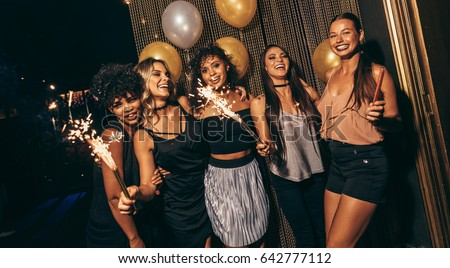 Happy multiethnic friends holding sparkling sticks at nightclub. Young people having fun at disco. #642777112