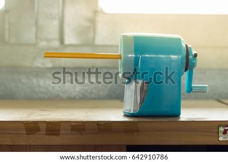 Mechanical pencil sharpener on wooden desk Royalty-Free Stock Photo #642910786