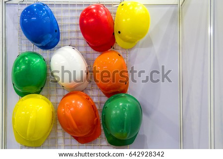Multi-colored helmet hanging over the wall. #642928342