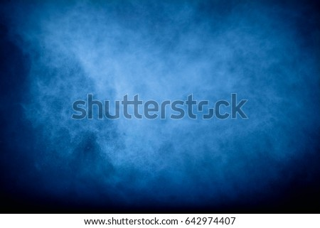 Abstract art blue powder on black background. Frozen abstract movement of dust explosion blue colors on black background. Stop the movement of blue powder on dark background.