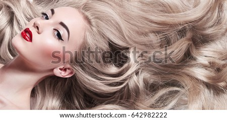 Beautiful young well-groomed girl lies - close-up. Long light shiny healthy well-groomed long hair. Advertising of hair care, cosmetics, beauty. Makeup - red lips, black arrows, mascara. #642982222