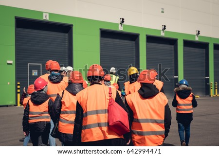 A group of people in orange helmets and reflective vests visiting factory or warehouse. From behind view. #642994471