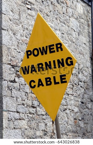 """Yellow diamond shaped warning sign saying """"Power Warning Cable"""" against a stone wall #643026838"""