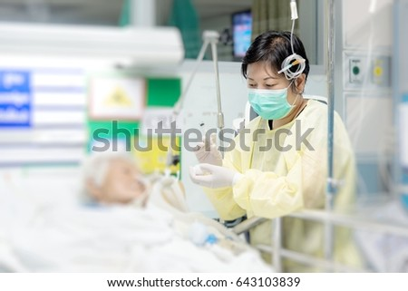 Asian women 40s years old in isolation gown non-sterile coat is a patient relative taking care of the CRE. or VRE. infected elder patient 80s years old on bed in the hospital. #643103839