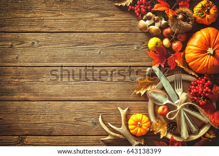 Autumn background from fallen leaves and fruits with vintage place setting on old wooden table. Thanksgiving day concept #643138399