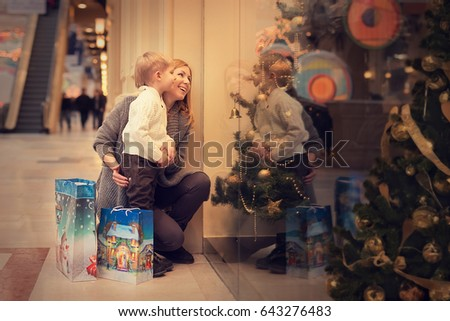 Mom with son are choosing gifts for Christmas and new year #643276483