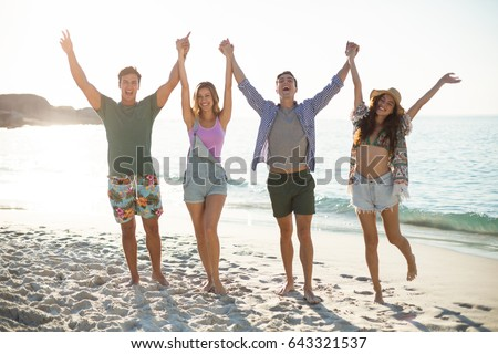 Full length of happy friends holding hands with arms raised on shore at beach #643321537