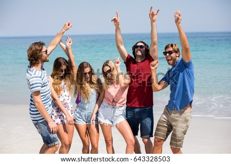Cheerful young friends dancing on shore at beach during sunny day #643328503
