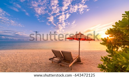 Romantic beach sunset with deck chairs and sun umbrella. Exotic tourism vacation banner design #643472125