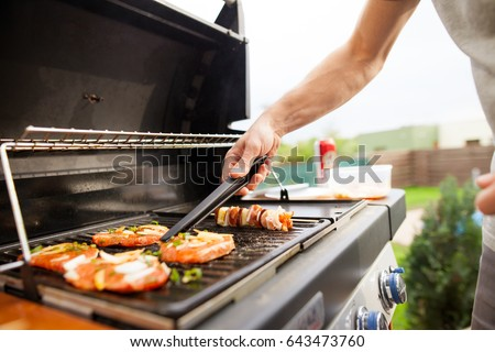 Hand of young man grilling some meat and vegetable-meat skewers on huge gas grill (Shallow DOF) Royalty-Free Stock Photo #643473760