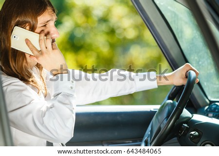 Talking while drive, danger fresh driver concept. Young man driving car using his smartphone, talking with someone. #643484065