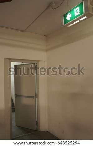 emergency exit sign and opened exit door in the old building #643525294
