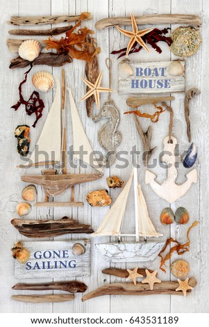 Abstract background with decorative sailing boats, signs, seashells, driftwood, seaweed and rocks on distressed white wood.