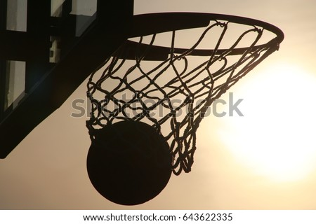 Basketball Going into Hoop Outdoors Late in the Afternoon in Silhouette against Yellow Sky Backlit by the Setting Sun #643622335
