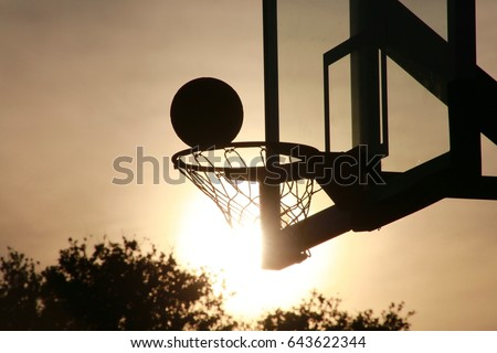 Basketball Going into Hoop Outdoors Late in the Afternoon in Silhouette against Yellow Sky Backlit by the Setting Sun #643622344