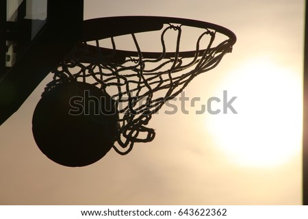 Basketball Going into Hoop Outdoors Late in the Afternoon in Silhouette against Yellow Sky Backlit by the Setting Sun #643622362