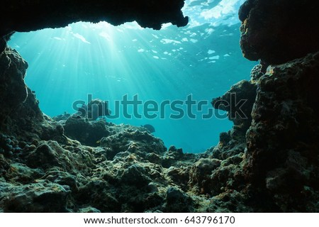 Underwater sunlight through water surface from a hole in a rocky ocean floor, natural scene, Pacific ocean, outer reef of Huahine, French Polynesia #643796170