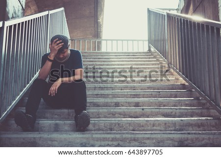 Depressed man sitting head in hands on the footbridge, Sad man, Cry, drama concept #643897705