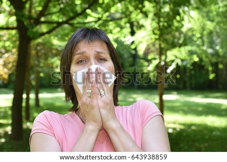 Woman with allergy symptom blowing her nose #643938859