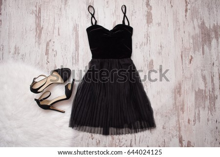 Little black dress and black shoes. Wooden background, fashionable concept #644024125