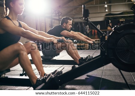 Side view of man and woman doing exercises with rowing machine at gym. Royalty-Free Stock Photo #644115022