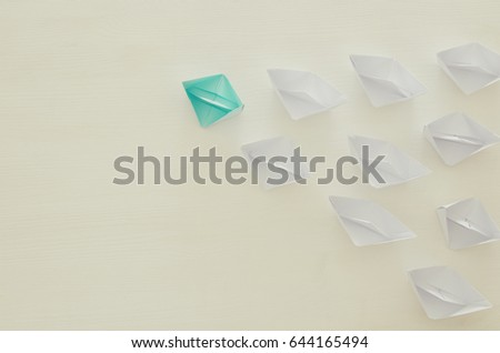 top view image of paper boats over wooden background and one individual boat choosing different path. unique and individuality concept #644165494