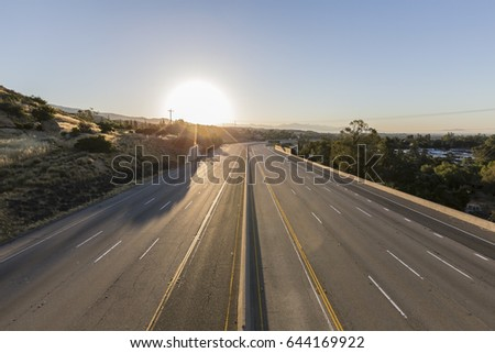 Empty ten lane route 118 freeway at sunrise in the San Fernando Valley area of Los Angeles, California. Royalty-Free Stock Photo #644169922