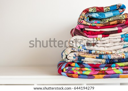 sewing and fashion concept - stack of colorful quilts, beautiful bedspreads stacked in several rows in height for storage, sale patchwork productions on a white background, copy space #644194279