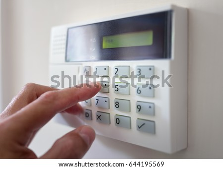 Security alarm keypad with person arming the system concept for crime prevention Royalty-Free Stock Photo #644195569
