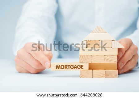Mortgage concept. Financial agent complete wooden model of the house with last piece with text mortgage. #644208028