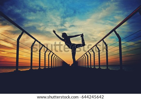 Silhouette of young woman meditating in yoga pose while exercising on the pier with amazing sunrise view on background #644245642