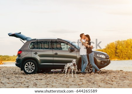 Family of two person and dog embrace near car on sunset river #644265589