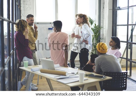 Crew of professional graphic designers having informal meeting with prosperous leader making workshop explaining information about startup project making discussing with staff members in modern studio #644343109