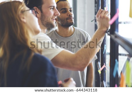 Young male and female coworkers writing remaining notes for colleagues planning productive working process in office, smiling students making memo stickers with to do list to organize daily schedule