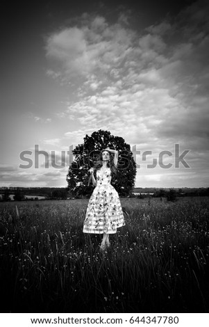 A beautiful young free girl in a light dress with lemons and a bouquet of wildflowers, in the middle of a spacious field with a large tree in the middle of it, with sky and clouds on a sunny day. #644347780