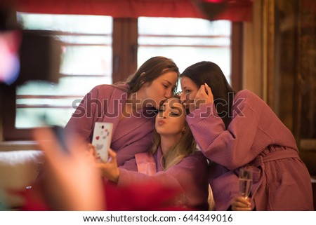 three young beautiful happy girls doing Selfy on bachelorette party at a luxury spa with champagne #644349016