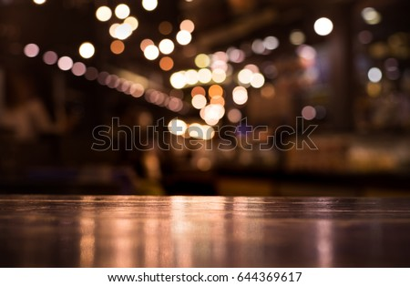 Wood table top with reflect on blur of lighting in night cafe,restaurant background/selective focus. Royalty-Free Stock Photo #644369617